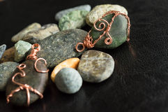 Two wire wrapped pendants among stones Royalty Free Stock Image