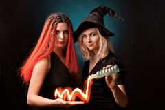 Two witches. Practises witchcraft on black background Royalty Free Stock Photo