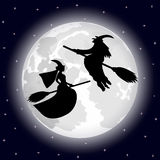 Two witches on a background of the full moon on Halloween night Stock Image
