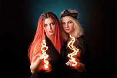 Two witches  practises witchcraft. Two witches practises witchcraft on black background Royalty Free Stock Photos