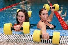 Two womam in water with dumbbells Royalty Free Stock Images
