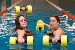 Two womam in water with dumbbells Royalty Free Stock Photos
