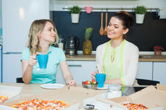 Two woman bakers have a snack on kitchen with pizza Royalty Free Stock Photos