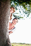 Two Woman behind a Tree Royalty Free Stock Image