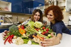Two Woman with a big pile of vegetables Stock Photo