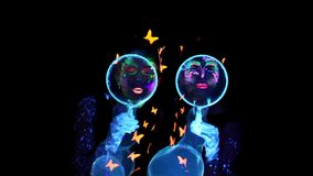 Two woman blowing bubbles in camera. Video of two woman with luminous make up blowing bubbles in camera in darkness stock video