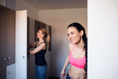Two woman changing in locker room in gym Stock Images
