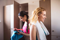 Two woman changing in locker room in gym Stock Photos