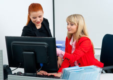 Two woman colegues working on computer in office Stock Images