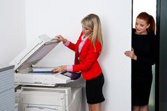 Two woman colleagues working on printer in office Royalty Free Stock Photography