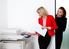 Two woman colleagues working on printer in office Royalty Free Stock Image