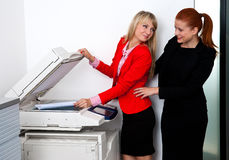 Two woman colleagues working on printer in office Stock Photography