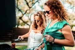 Two woman cooking at barbecue party, having drinks and smiling royalty free stock image