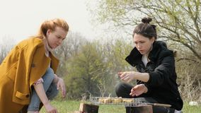 Two woman during cooking meat barbecue on fire at picnic on nature. Process cooking food on fire during trekking to nature on summer trip stock footage