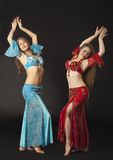 Two woman dance and smile in arabian costume Royalty Free Stock Images