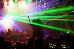 Two woman dancing on a platform. Between laserlight in an underground-club royalty free stock photography