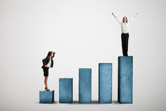 Two woman on the diagram. Businesswoman standing at the lower step of diagram and looking up at the winner over light grey background Stock Photos