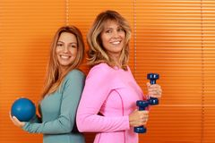 Two woman of different ages with sport equipment in front of orange background. Two happy women of different ages with sport equipment in front of orange royalty free stock photography