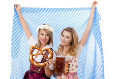 Two woman with dirndl and bavarian flag Royalty Free Stock Photography