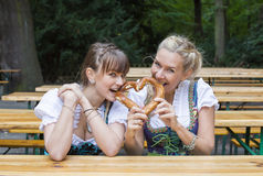 Two woman in dirndl with pretzel. Two women in dirndl in beer garden with pretzel royalty free stock image