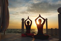 Two women do yoga at sunrise near the sea. A two woman do yoga at sunrise near the sea Royalty Free Stock Photos