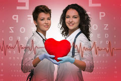Two woman doctor holding a red heart royalty free stock image