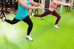 Two woman does suspension training with fitness straps in gym Stock Images