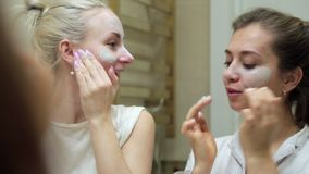 Two woman doing cosmetic mask on her face.  stock video