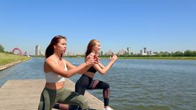Two woman doing the exercises sports on the banks of the river in the city. Exercises outdoor. Two woman doing the exercises sports on the banks of the river in stock footage