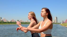 Two woman doing the exercises sports on the banks of the river in the city. Exercises outdoor. Two woman doing the exercises sports on the banks of the river in stock video