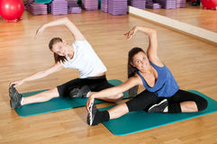 Two woman doing stretching exercise at gym Royalty Free Stock Photos