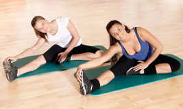 Two woman doing stretching exercise at gym Stock Photography