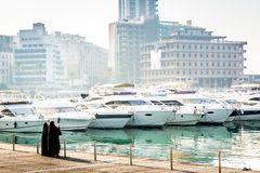 Two woman dressed with black arab traditional clothes in a marine bay full of modern boats with old buildings in the background. H stock image