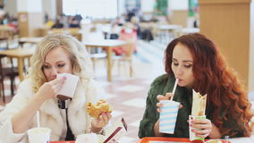 Two woman eating junk food. Two girl eating fast food stock footage