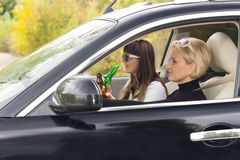 Two woman enjoying alcohol while driving Stock Images