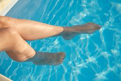 Two woman feet in blue pool Royalty Free Stock Photo