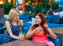 Two woman friends drinking juice in bar Royalty Free Stock Image