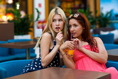 Two woman friends drinking juice in bar Stock Image
