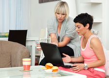 Two woman friends with laptop at home Royalty Free Stock Photos