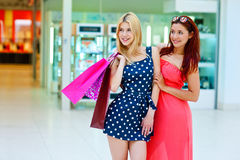 Two woman friends in shopping mall with bags Royalty Free Stock Photos
