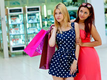 Two woman friends in shopping mall with bags Stock Photos