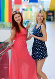 Two woman friends in shopping mall with credit cards Stock Photo