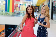 Two woman friends in shopping mall with credit cards Royalty Free Stock Photos