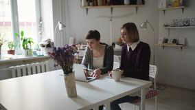 Two woman friends spend leisure and using notebook sitting at table. Two woman friends spend leisure and using notebook for chatting. Two woman chatting online stock footage
