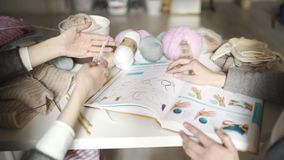 Two woman friends using book with knitting pattern. Knitting needles. Two woman friends using book with knitting pattern. Closeup of female hands studying to stock video footage