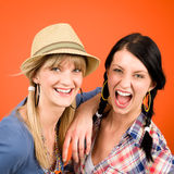 Two woman friends young crazy smile. Two women friends young crazy smile portrait on orange background Royalty Free Stock Photography