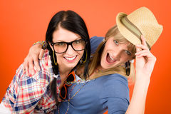 Two woman friends young have fun crazy. Two women friends young have fun crazy smiling orange background Stock Photo