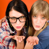 Two woman friends young sending kisses. Two women friends young sending kisses smiling crazy outfit Royalty Free Stock Photography