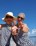 Two woman giving  thumbs up. Portrait of two happy woman (best friends) dressed in sailors clothes, with sunglasses laughing and giving the thumbs-up sign, near Royalty Free Stock Image