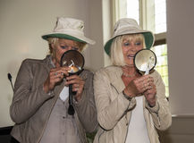 Two woman with hand holding magnifying glass Stock Photography
